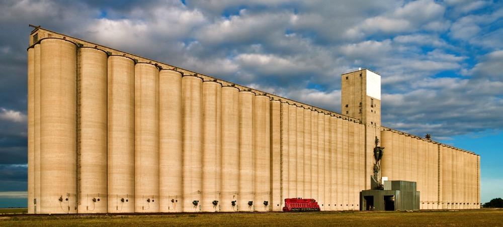 huge grain elevator dwarfs train locomotive