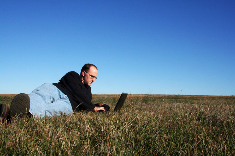 man using a laptop computer in a field