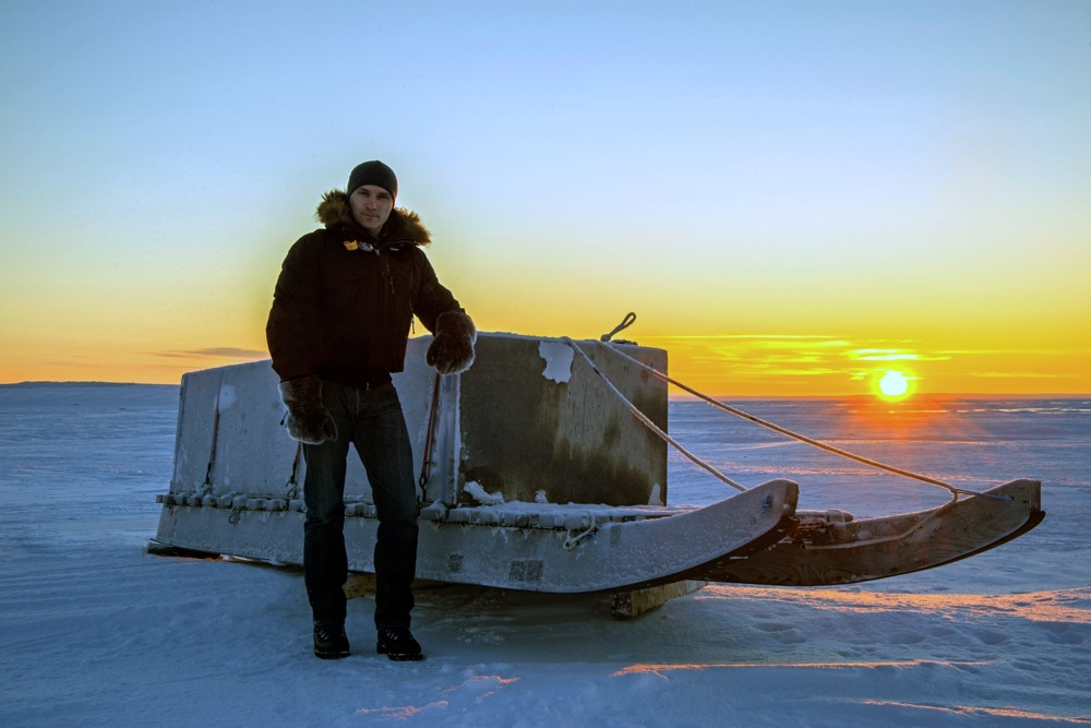 man on arctic ice with sled
