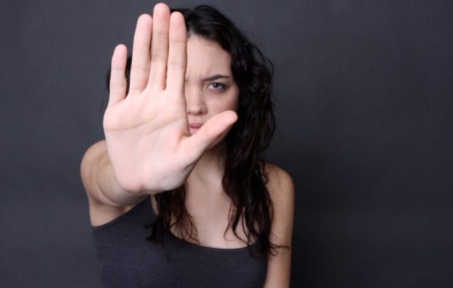 angry girl holds up her hand to stop predator and end the cycle of abuse