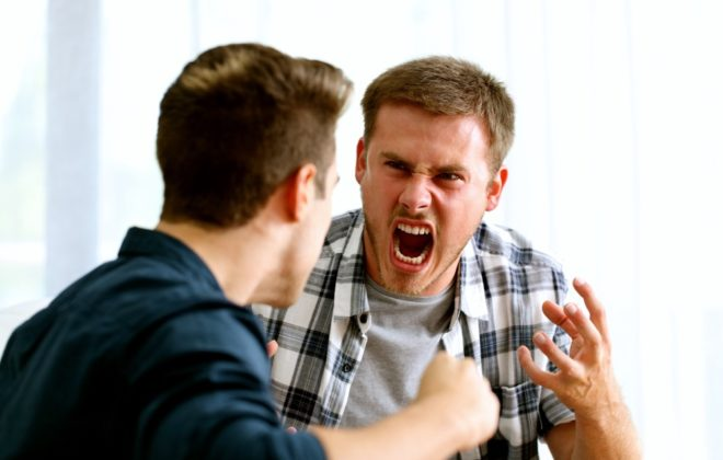 Two angry friends or roommates arguing and threatening in the living room at home