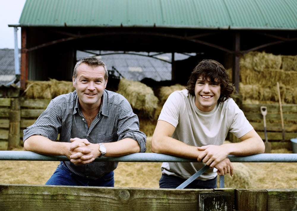 Farmer and His Son Standing Side by Side Leaning on a Gate