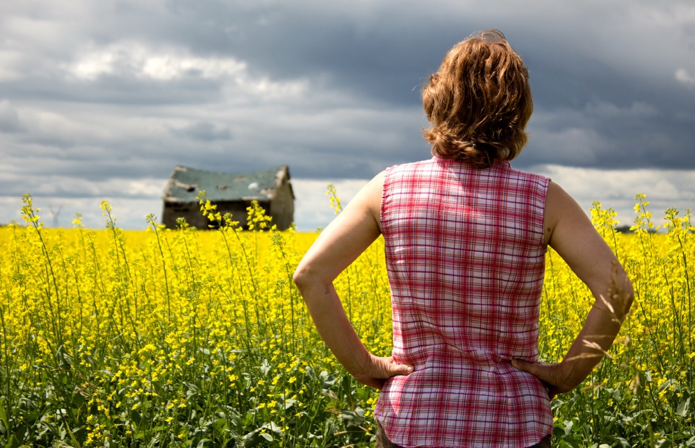 backside of woman looking over canola field at rain clouds