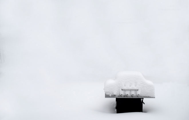 Snow covered outdoor grill during a winter snowstorm frozen cold bar-be-que white-out background type space