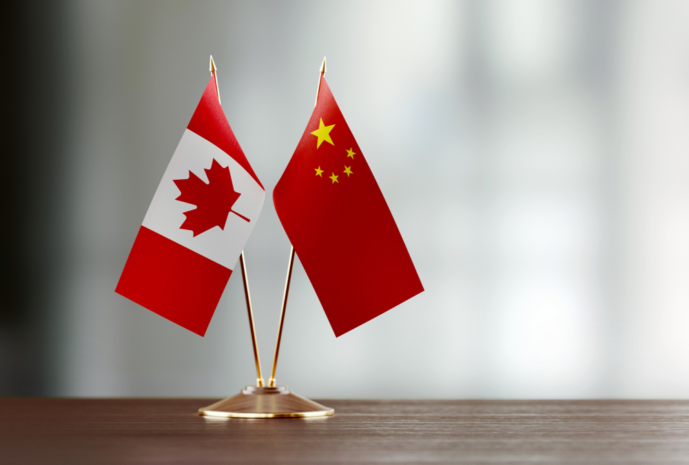 Canadian and Chinese flag pair on desk over defocused background. Horizontal composition with copy space and selective focus.