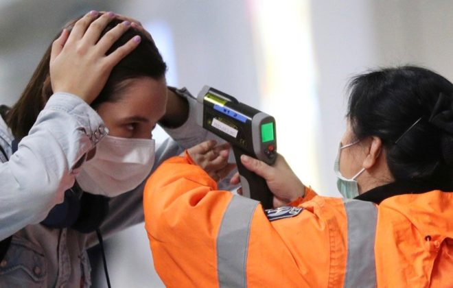 A worker checks the temperature of a passenger arriving into Hong Kong International Airport with an infrared thermometer on Feb. 7, 2020. (Photo: Reuters/Hannah McKay)
